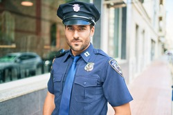 young handsome hispanic policeman wearing police uniform. Standing with serious expression at town street.