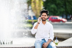 Young handsome indian man speak on phone sitting near fountain in the sunny summer day