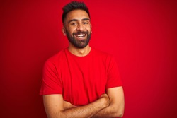 Young handsome indian man wearing t-shirt over isolated red background happy face smiling with crossed arms looking at the camera. Positive person.