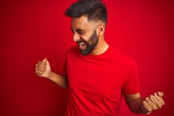 Young handsome indian man wearing t-shirt over isolated red background very happy and excited doing winner gesture with arms raised, smiling and screaming for success. Celebration concept.
