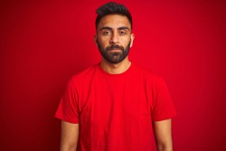 Young handsome indian man wearing t-shirt over isolated red background with serious expression on face. Simple and natural looking at the camera.