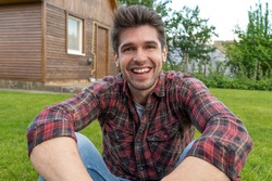 Young handsome latin guy with a big smile chilling on the grass outside