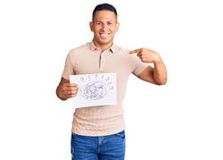Young handsome latin man holding scribble draw pointing finger to one self smiling happy and proud