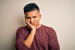 Young handsome latin man wearing casual sweater standing over isolated white background thinking looking tired and bored with depression problems with crossed arms.