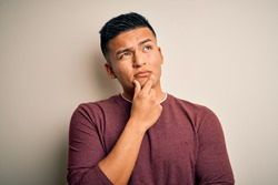 Young handsome latin man wearing casual sweater standing over isolated white background with hand on chin thinking about question, pensive expression. Smiling with thoughtful face. Doubt concept.