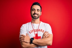 Young handsome lifeguard man with beard wearing whistle over isolated red background happy face smiling with crossed arms looking at the camera. Positive person.