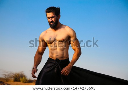 Young handsome long hair and beard Asian muscled fit male model man posing outdoor against blue sky showing his abdominal muscles - Image