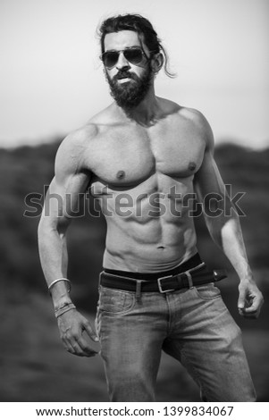 Young handsome long hair and beard Asian muscled fit male model man posing outdoor showing his abdominal muscles black and white - Image