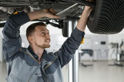 Young handsome male auto mechanic working on car undercarriage using a wrench positivity professionalism experience safety motors automotive transport technology service instruments tools concept