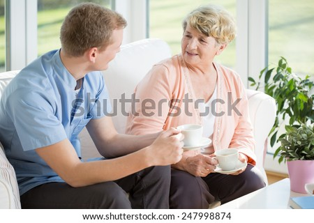 Young handsome male nurse and senior woman during tea time