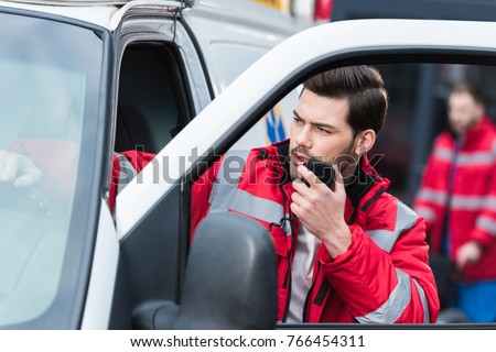 young handsome male paramedic standing near ambulance and talking by portable radio #766454311