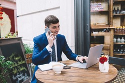 Young handsome male wearing elegant blue suit and striped tie smiling and looking at laptop while talking on phone, sitting on cafe terrace
