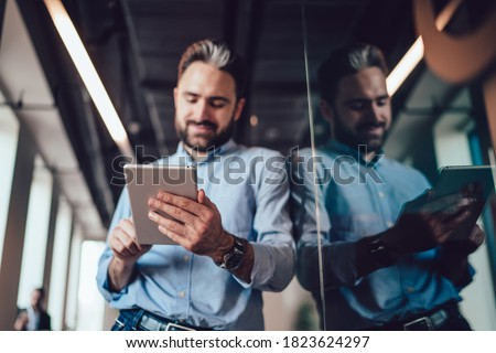 Young handsome male with beard in classic formal wear focused on devise standing near glass wall with reflection and looking away Stock photo ©