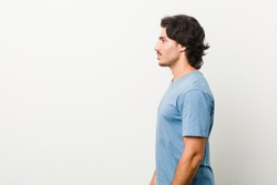 Young handsome man against a white background gazing left, sideways pose.