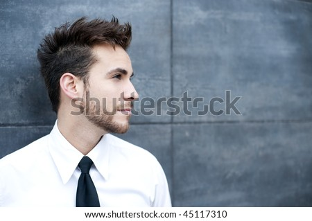 Young handsome man against wall