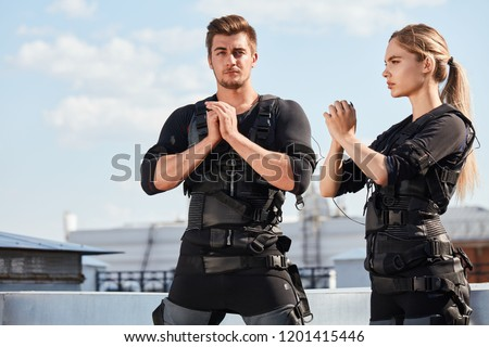 Young handsome man and a beautiful woman in an electric muscular suit are training to stimulate themselves on the street.