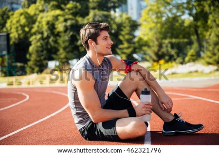 Young handsome man athlete resting with earphones at the stadium and drinking water
