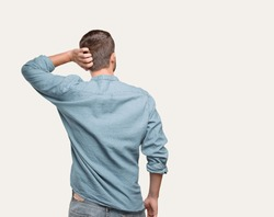 young handsome man, blue denim shirt, back pose and thinking or doubting . person isolated against monochrome background