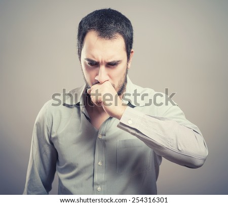 Young handsome man covered her mouth in surprise. Gesture. On a gray background