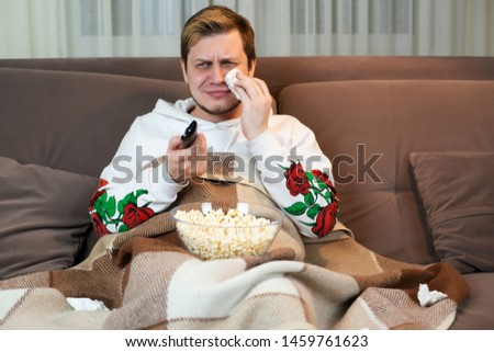 young handsome man crying while watching touching movie with popcorn on the comfy sofa