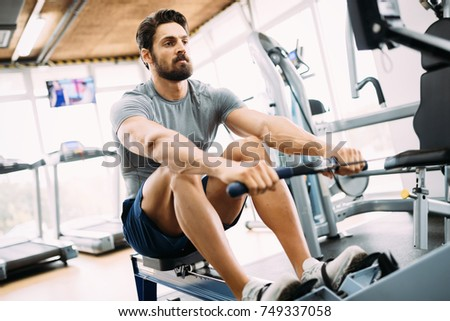 Young handsome man doing exercises in gym stock photo