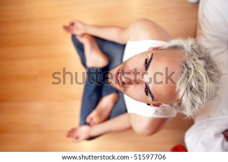 Young handsome man doing yoga on the floor