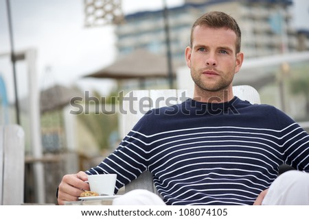 Young handsome man drinking coffee at a seaside beach restaurant.