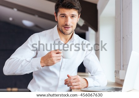 Young handsome man drinking coffee in office and looking at camera