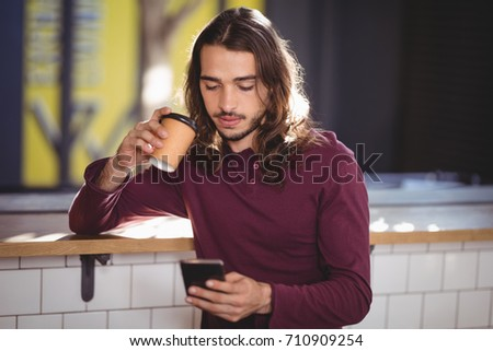 Young handsome man drinking coffee while using smartphone at cafe
