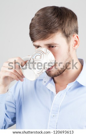 Young, handsome man drinking from a mug