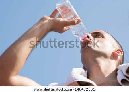 Young handsome man drinking water.