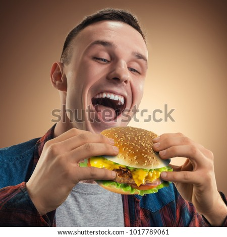 Young handsome man eating a hamburger. Portrait of a happy guy with a hamburger in his hands. Advertising fast food. Tasty cheeseburger. #1017789061