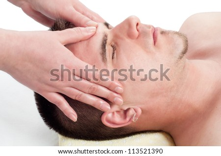 Young handsome man enjoying the facial massage on massage table.
