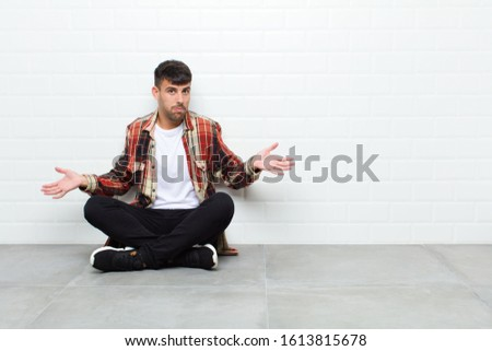 young handsome man feeling clueless and confused, having no idea, absolutely puzzled with a dumb or foolish look sitting on cement floor