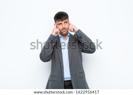 young handsome man feeling confused or doubting, concentrating on an idea, thinking hard, looking to copy space on side against white wall