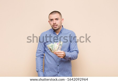 young handsome man feeling puzzled and confused, with a dumb, stunned expression looking at something unexpected with dollar banknotes