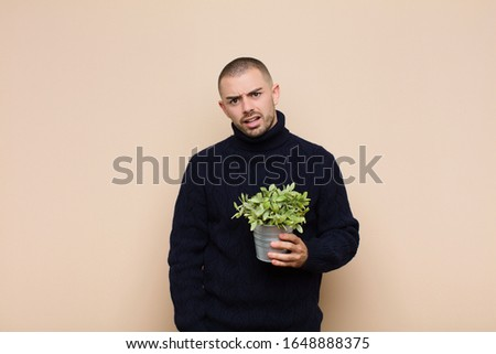 young handsome man feeling puzzled and confused, with a dumb, stunned expression looking at something unexpected holding a plant