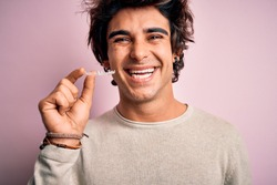 Young handsome man holding aligner standing over isolated pink background with a happy face standing and smiling with a confident smile showing teeth