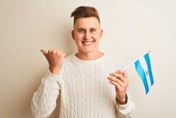 Young handsome man holding Argentinian Argentina flag over isolated white background pointing and showing with thumb up to the side with happy face smiling