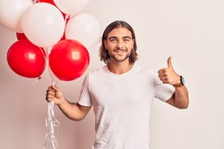 Young handsome man holding balloons smiling happy and positive, thumb up doing excellent and approval sign