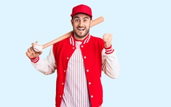 Young handsome man holding baseball bat and ball screaming proud, celebrating victory and success very excited with raised arms