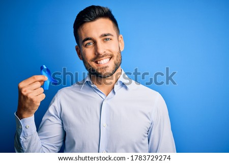 Young handsome man holding blue ribbon as prostate campaing support over blue background with a happy face standing and smiling with a confident smile showing teeth Foto stock ©
