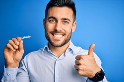 Young handsome man holding dental aligner tooth correction over blue background happy with big smile doing ok sign, thumb up with fingers, excellent sign
