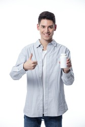 Young handsome man holding medicine pills standing over isolated white background smiling happy pointing with hand and finger
