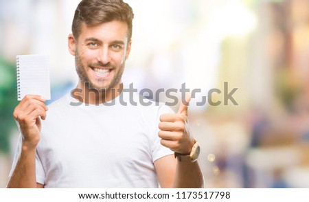 Young handsome man holding notebook over isolated background happy with big smile doing ok sign, thumb up with fingers, excellent sign #1173517798