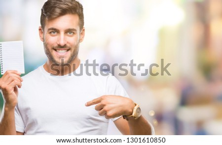 Young handsome man holding notebook over isolated background with surprise face pointing finger to himself #1301610850