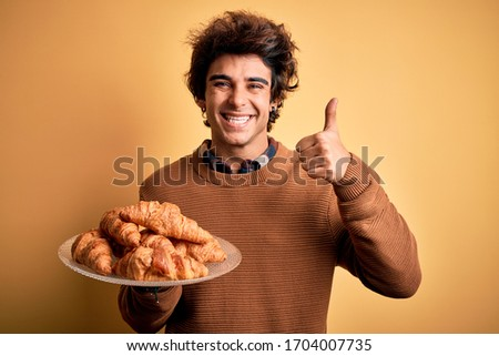 Young handsome man holding plate with croissants standing over isolated yellow background happy with big smile doing ok sign, thumb up with fingers, excellent sign Stock fotó ©