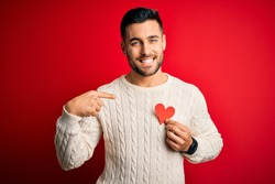 Young handsome man holding red shape heart as romantic and health symbol with surprise face pointing finger to himself