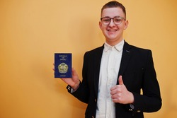 Young handsome man holding Republic of Nauru passport id over yellow background, happy and show thumb up.  Travel to Oceania country concept.