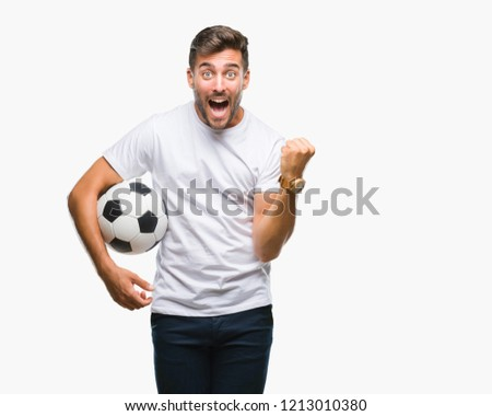 Young handsome man holding soccer football ball over isolated background screaming proud and celebrating victory and success very excited, cheering emotion